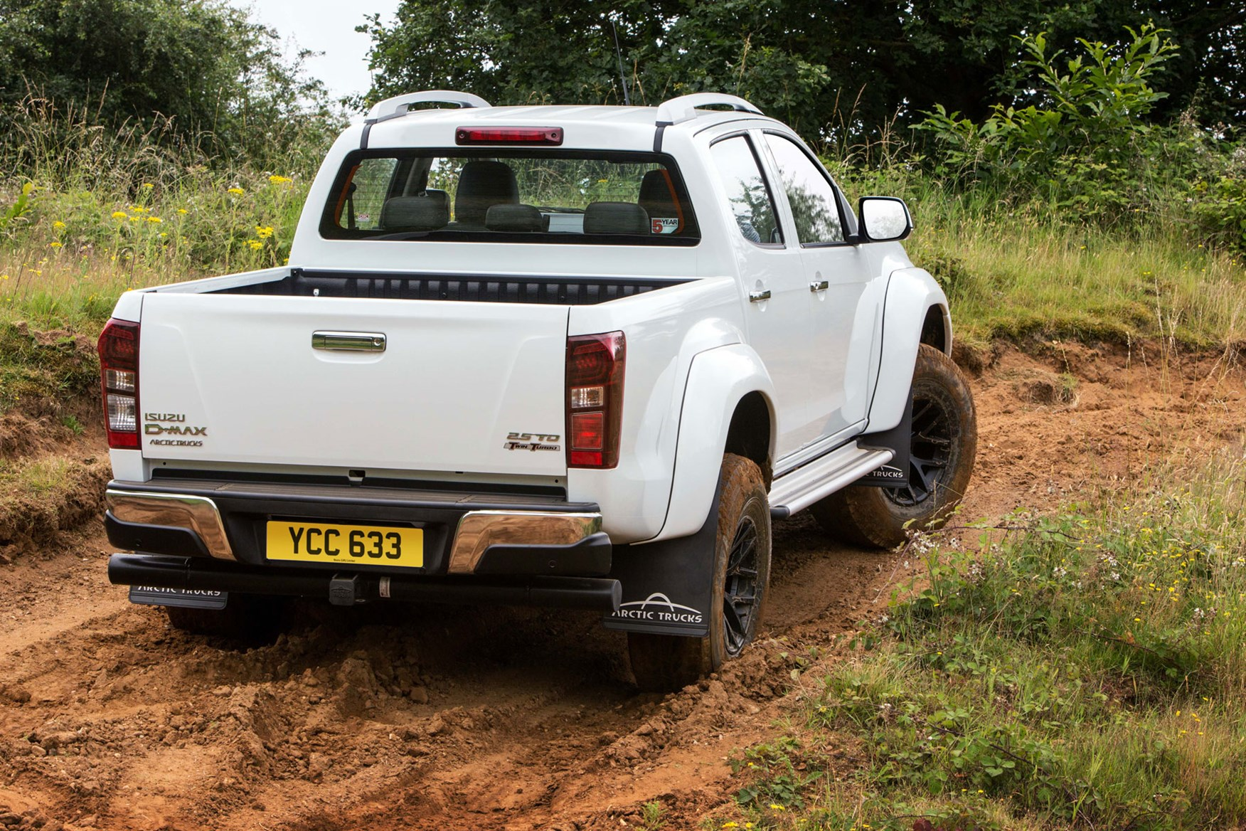 Isuzu D-Max AT35 2.5 review - rear view, driving up muddy hill, white