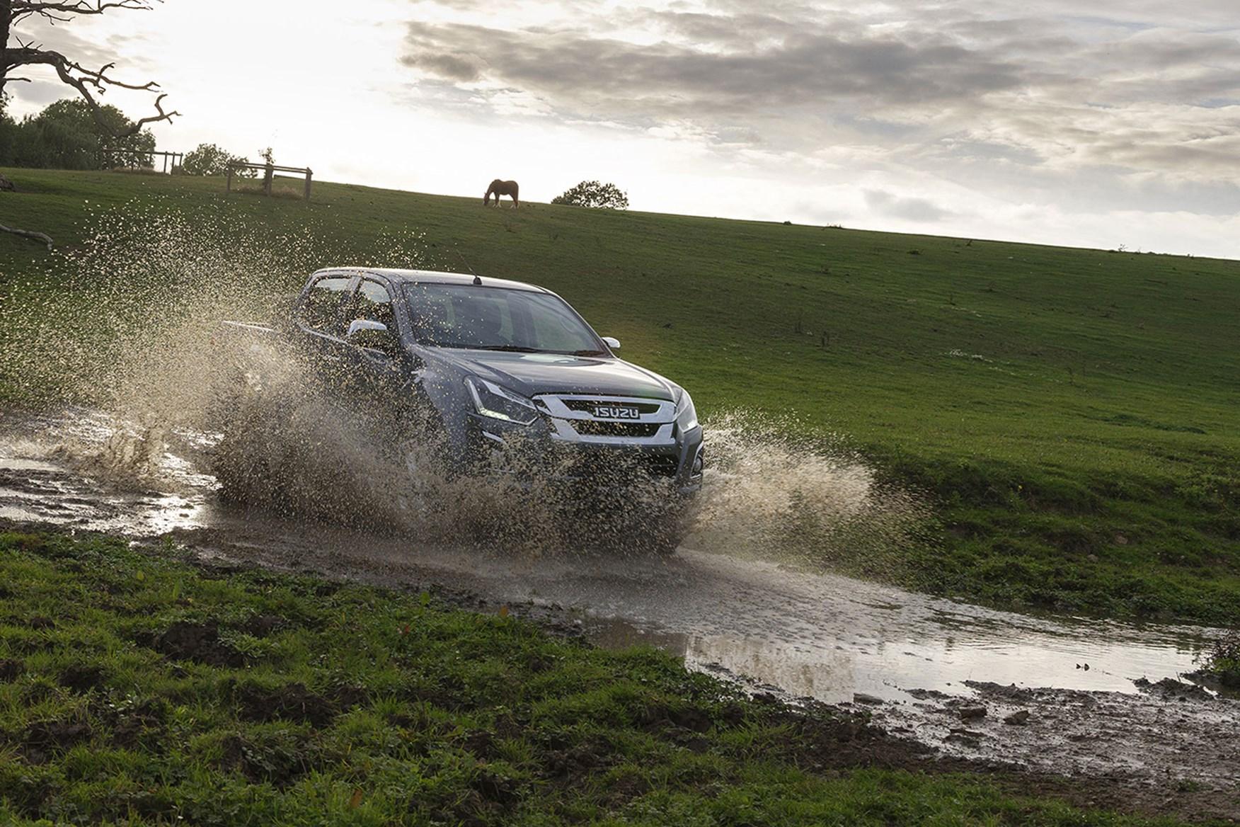 Isuzu D-Max Yukon review - splashing through water in field, grey