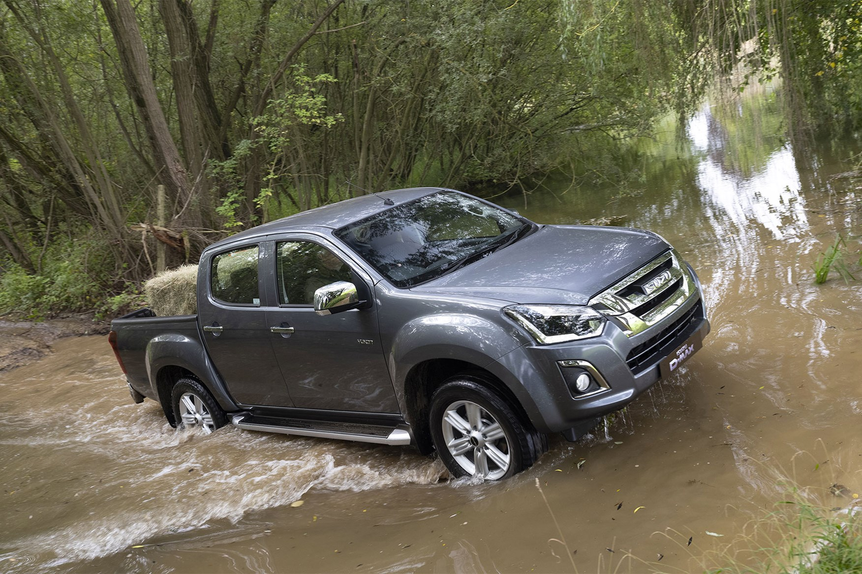 Isuzu D-Max off-road - splashing through river with hay bale in load area