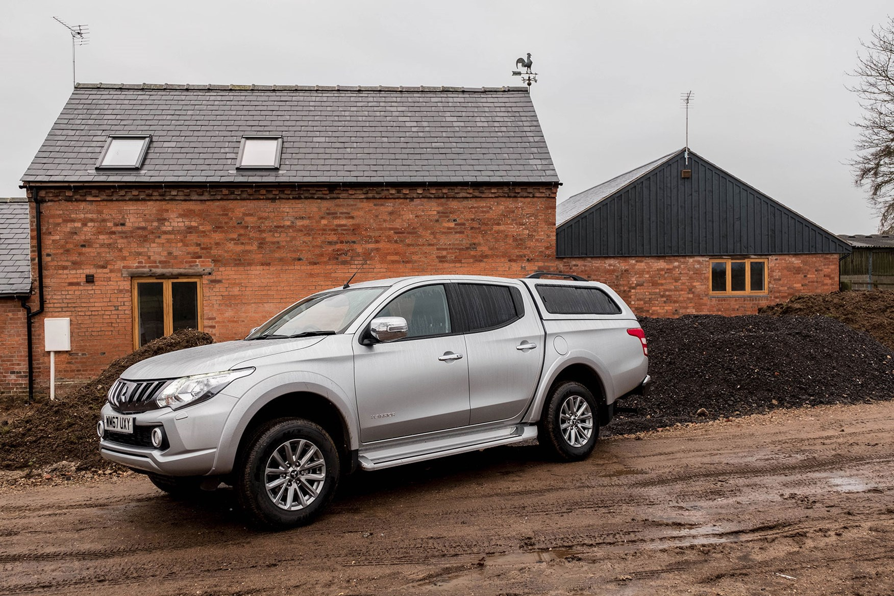 Mistubishi L200 Warrior 2018 review - side view, silver, rain, parked in front of farm building
