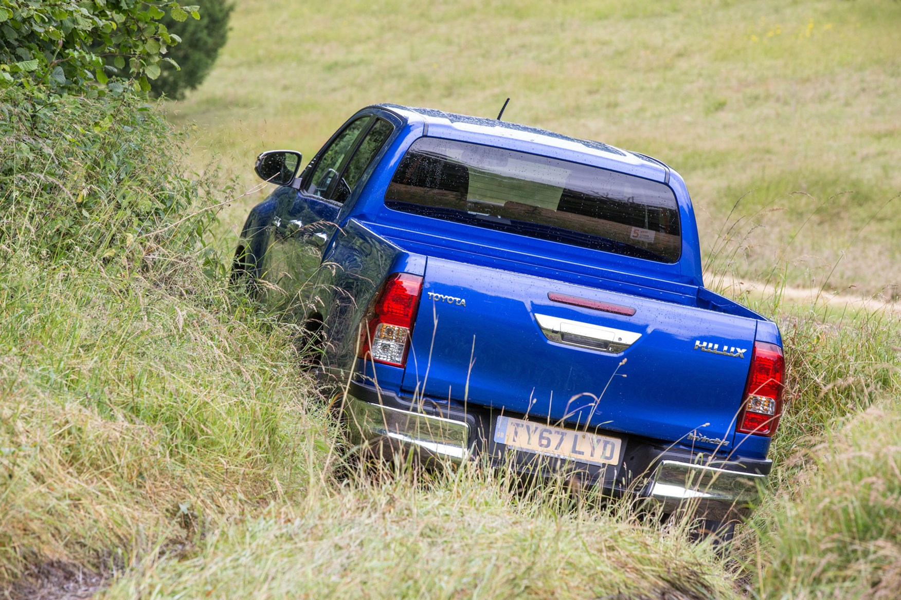 Toyota Hilux review - rear view, blue, driving off road