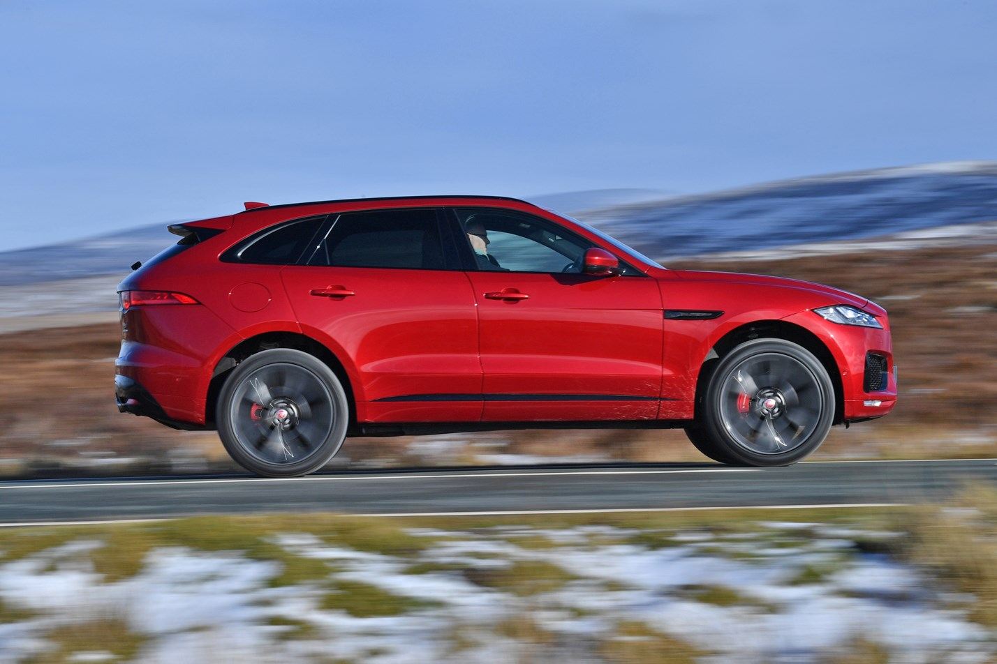 Red 2016 Jaguar F-Pace SUV side elevation driving