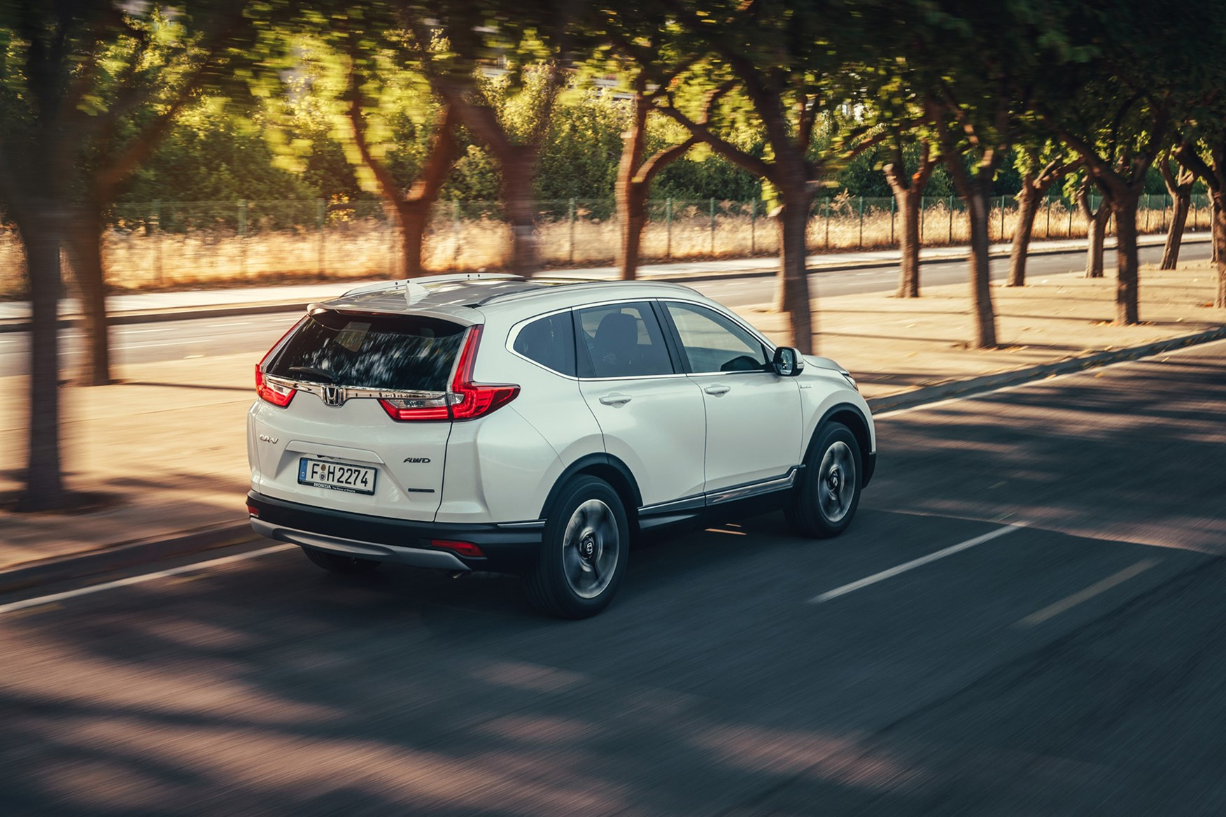 White 2019 Honda CR-V SUV Hybrid rear three-quarter driving