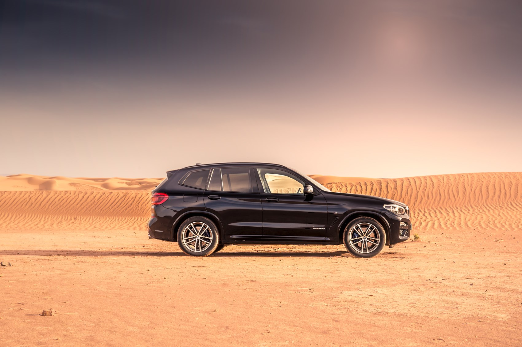 Black 2017 BMW X3 SUV side elevation on sand