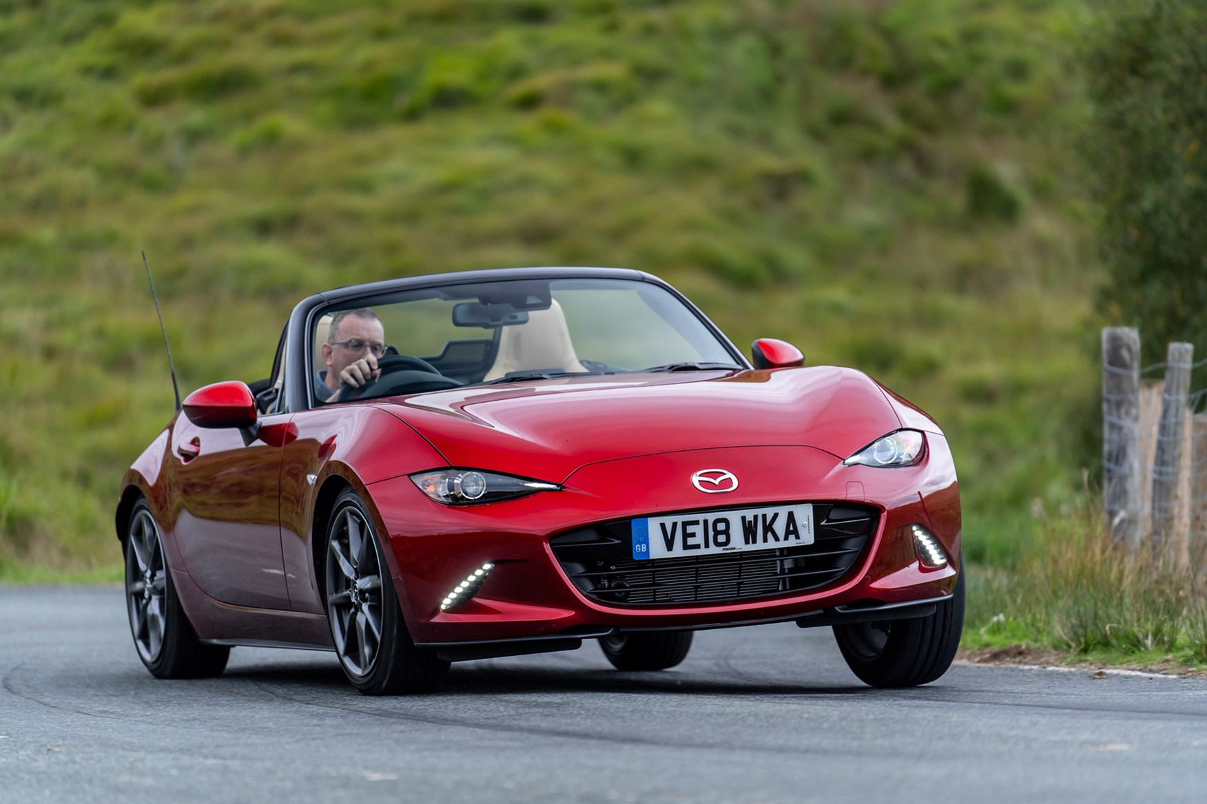 Mazda MX-5 red, roof open, driving front view