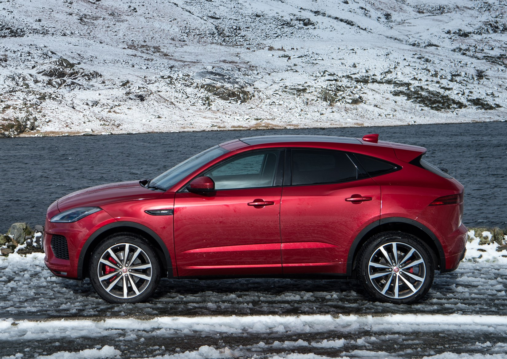 Red 2017 Jaguar E-Pace SUV side elevation in snow
