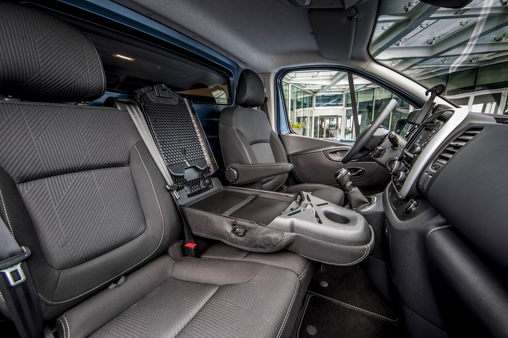 Renault Trafic review - 2019 facelift, cab interior showing seats and fold-down middle seat mobile office desk