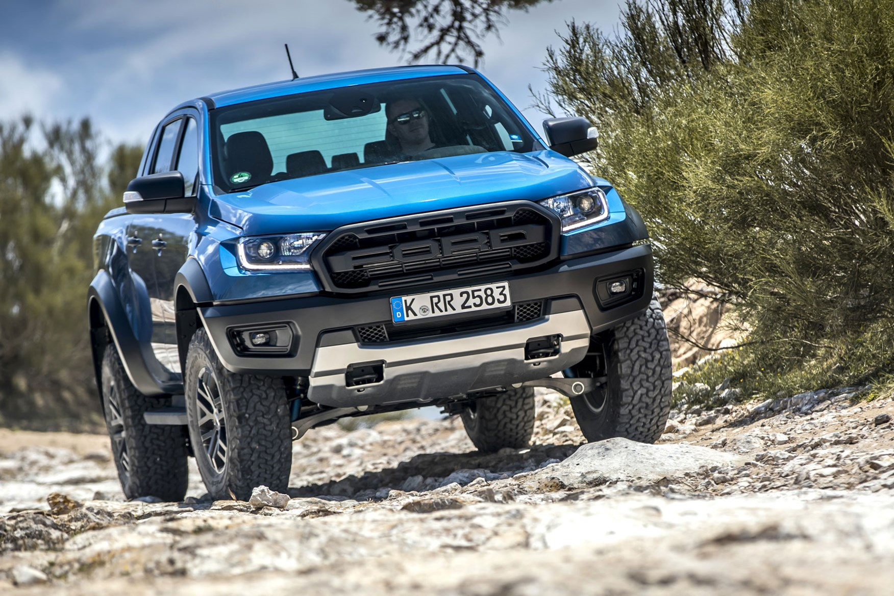 Ford Ranger Raptor high performance pickup truck - Performance Blue, front view, on rocks
