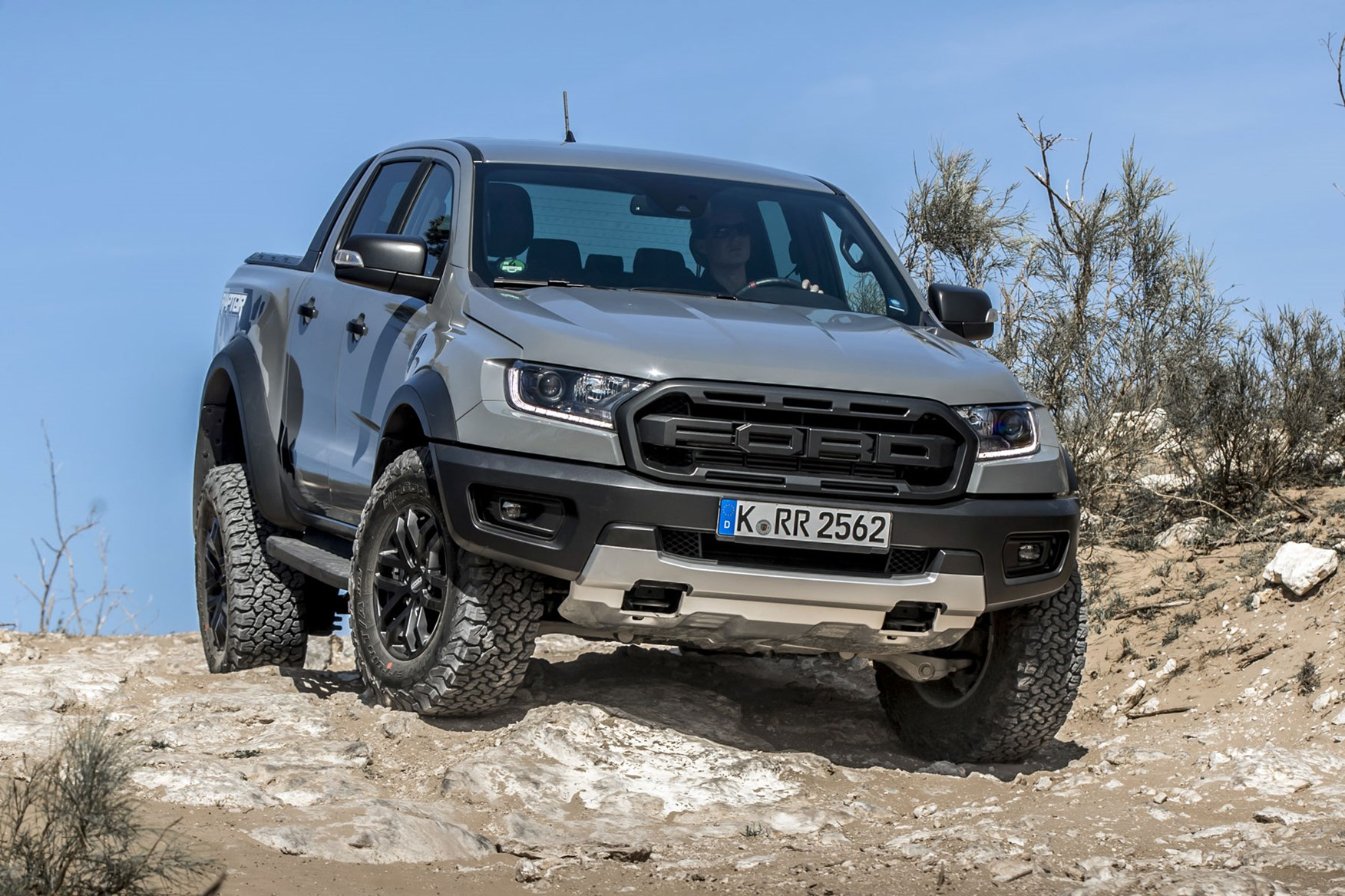 Ford Ranger Raptor - front view, Conquer Grey, parked on rocks showing off axle articulation