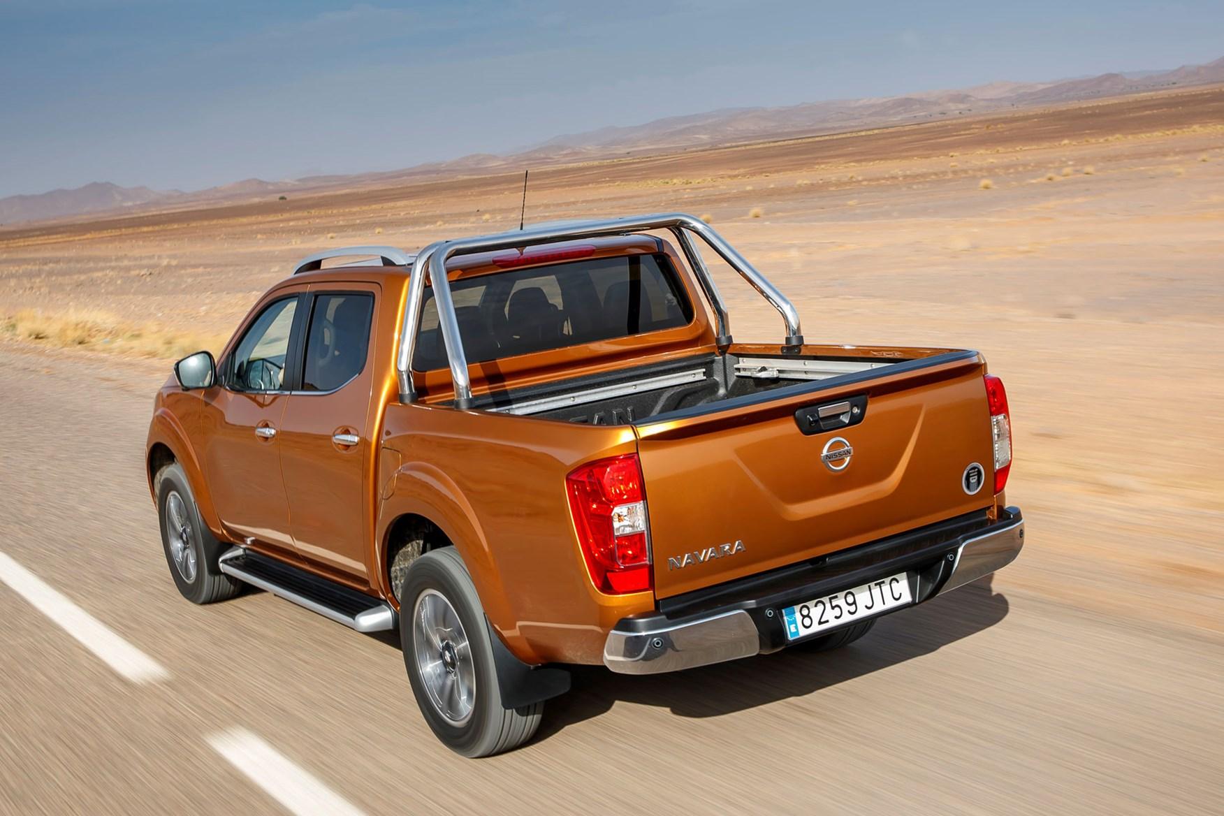 Nissan Navara Tekna review - rear view, driving on road, orange