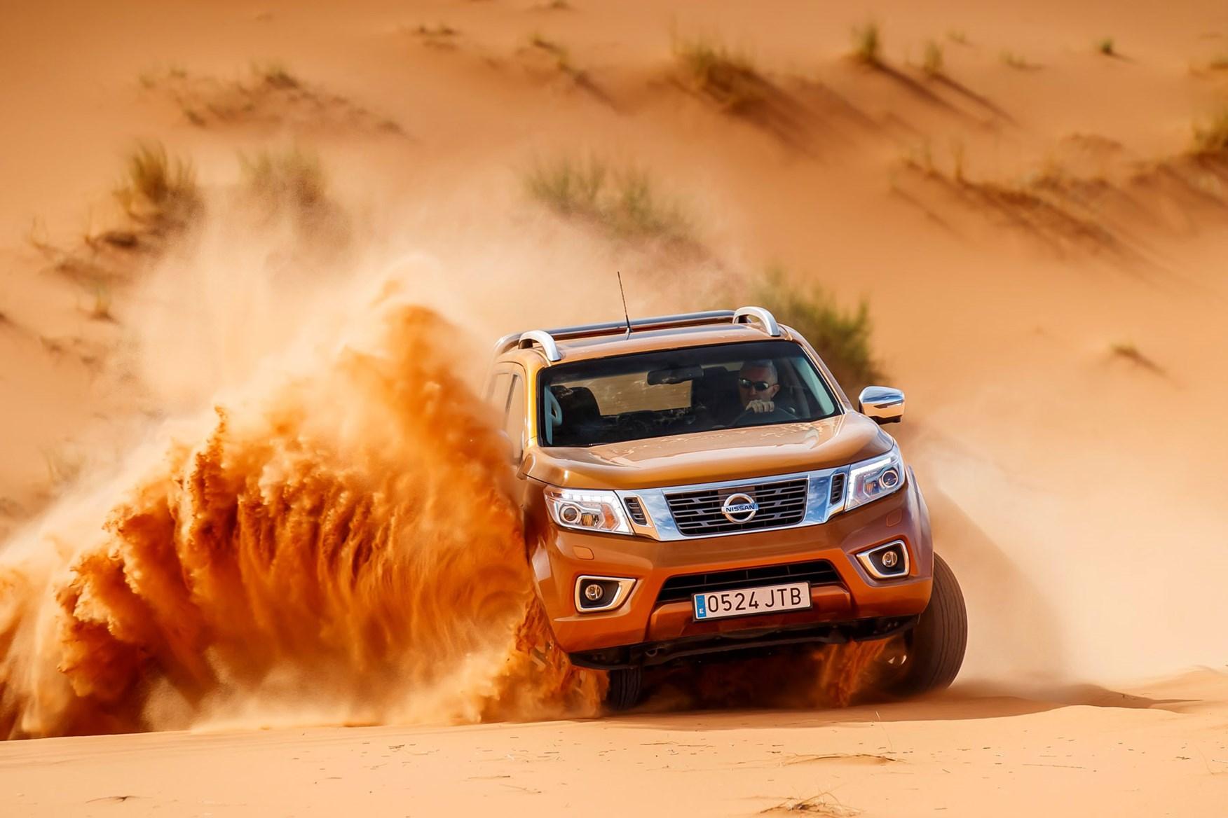 Nissan Navara Tekna review - driving in the Sahara Desert, front view, orange, spraying sand