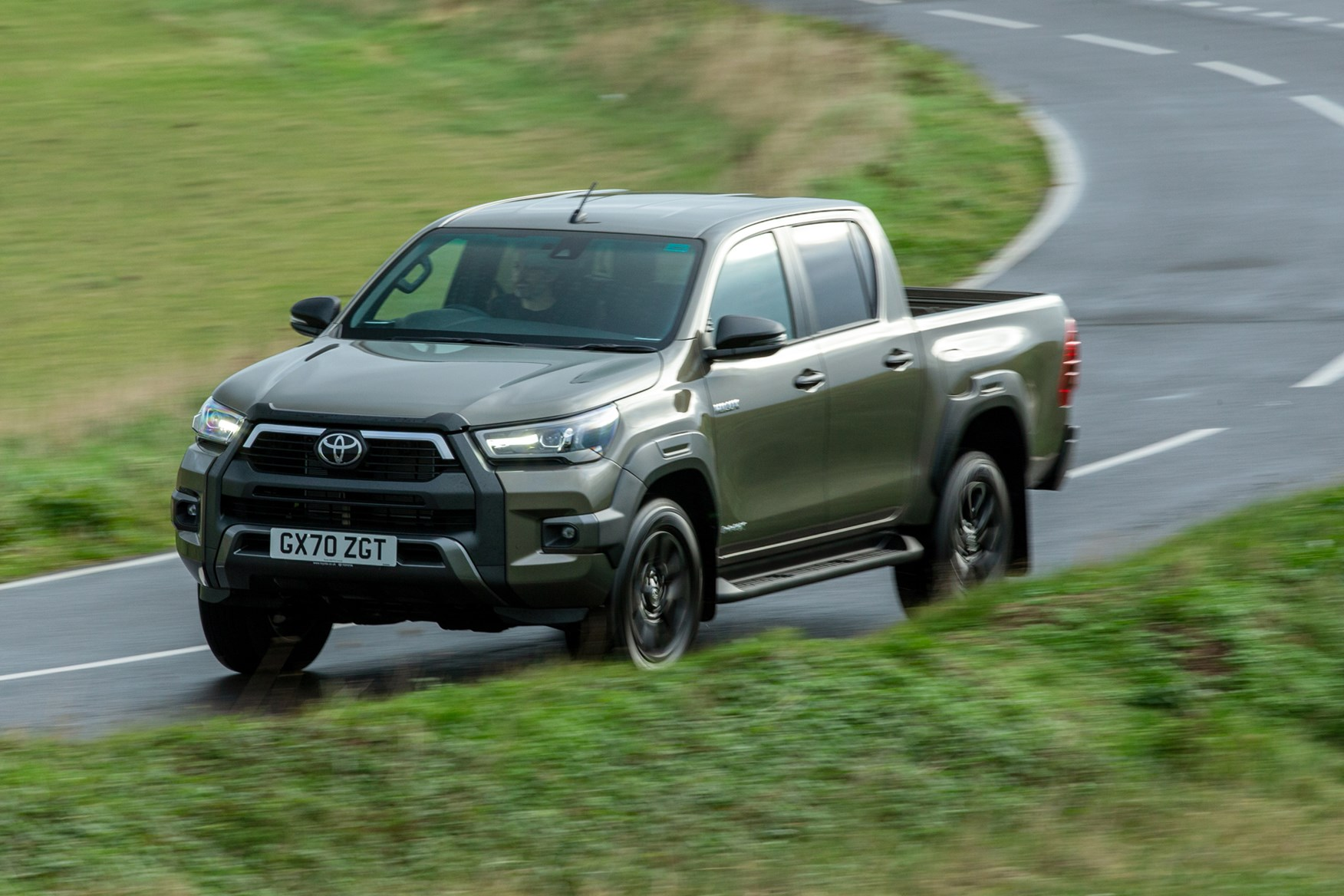Toyota Hilux review, 2020 facelift, Invincible X, driving round corner, front view, bronze