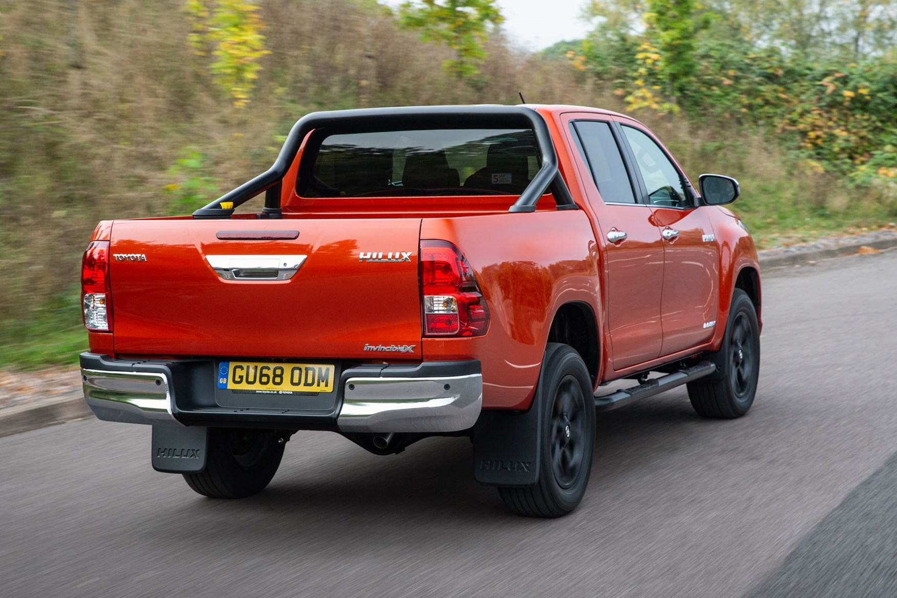 Toyota Hilux review - rear view, driving, Invincible X, orange