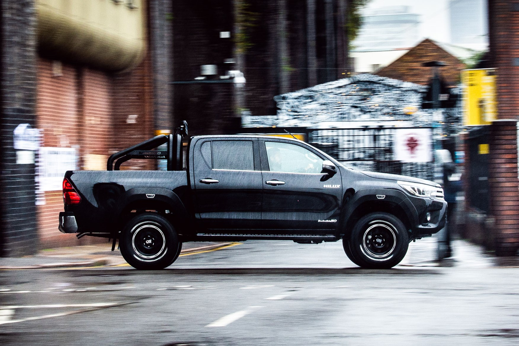 Toyota Hilux Invincible 50 review - driving, side view, in the rain