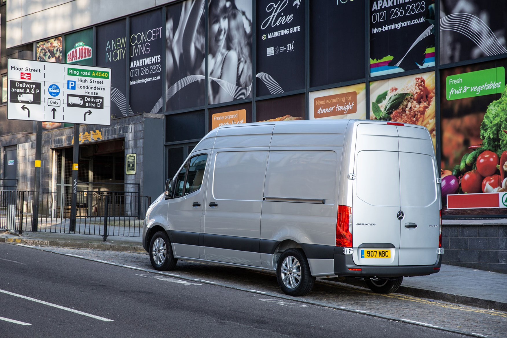 Mercedes Sprinter (2018-on), rear view, silver, UK, parked at junction with traffic signs, safety