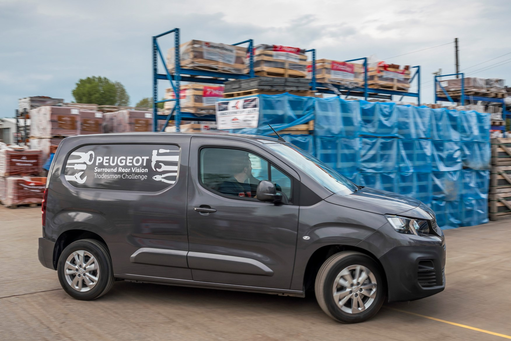 Peugeot Partner review 2020, side view, grey, driving round builders' yard