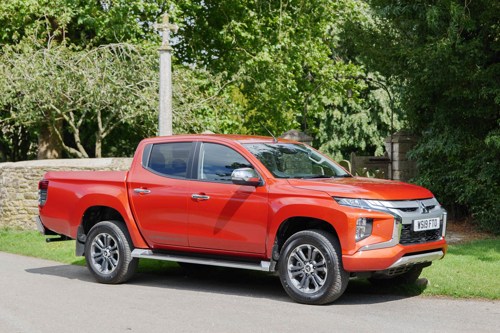 2019 Mitsubishi L200 Series 6, Sunflare Orange Barbarian X in a small village
