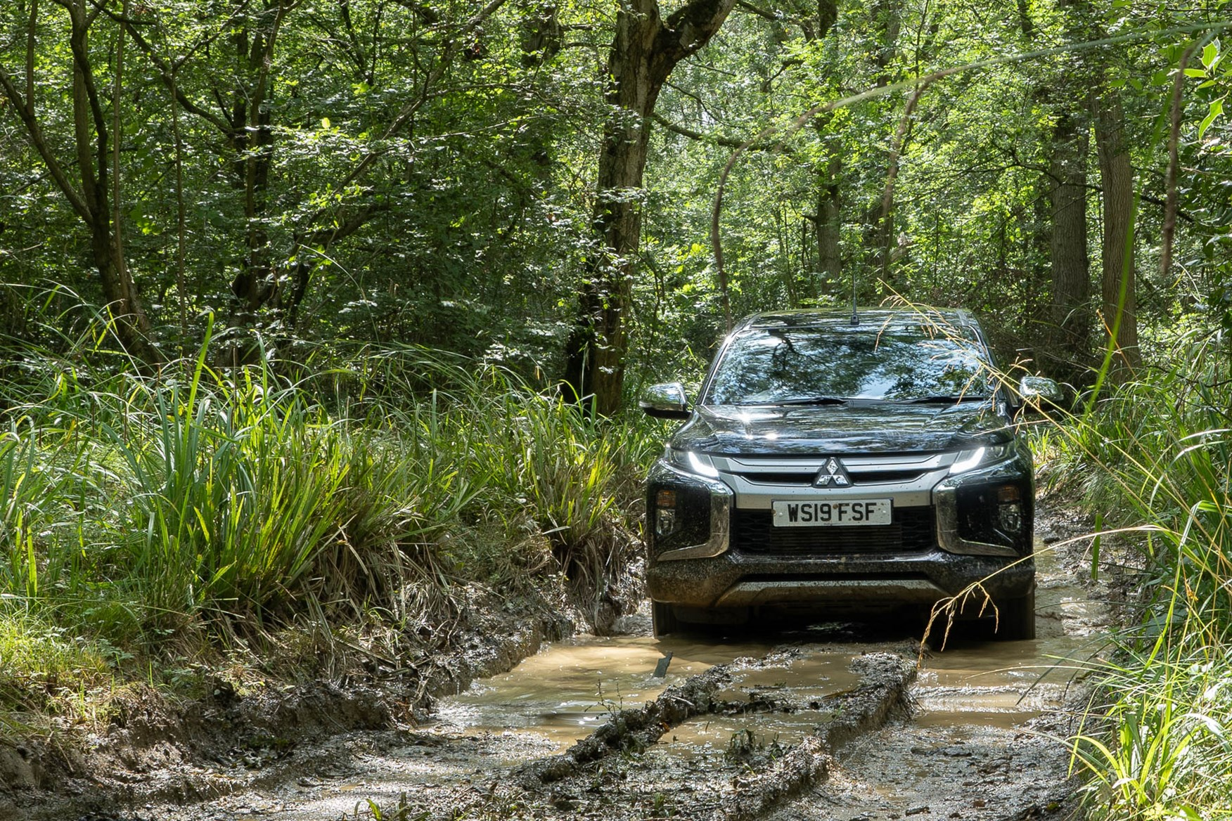 2019 Mitsubishi L200 4x4, Jet Black, on muddy forest track
