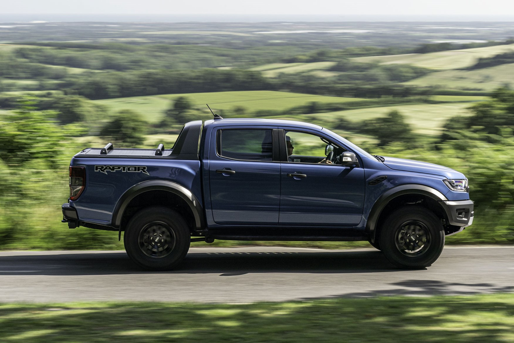 Ford Ranger Raptor review - side view, blue, driving on road, 2019