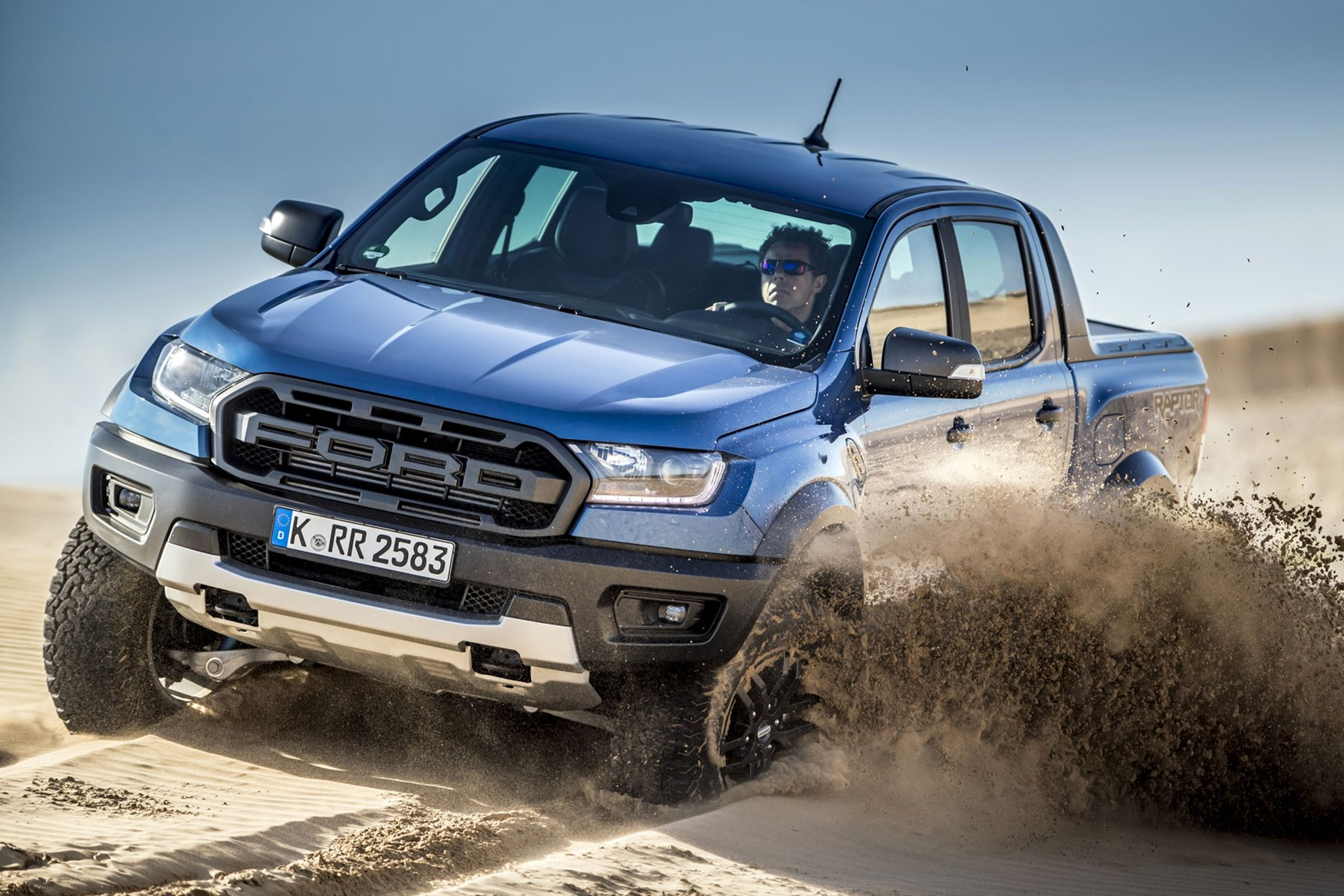 Ford Ranger Raptor review - front view, blue, smashing through sand, 2019