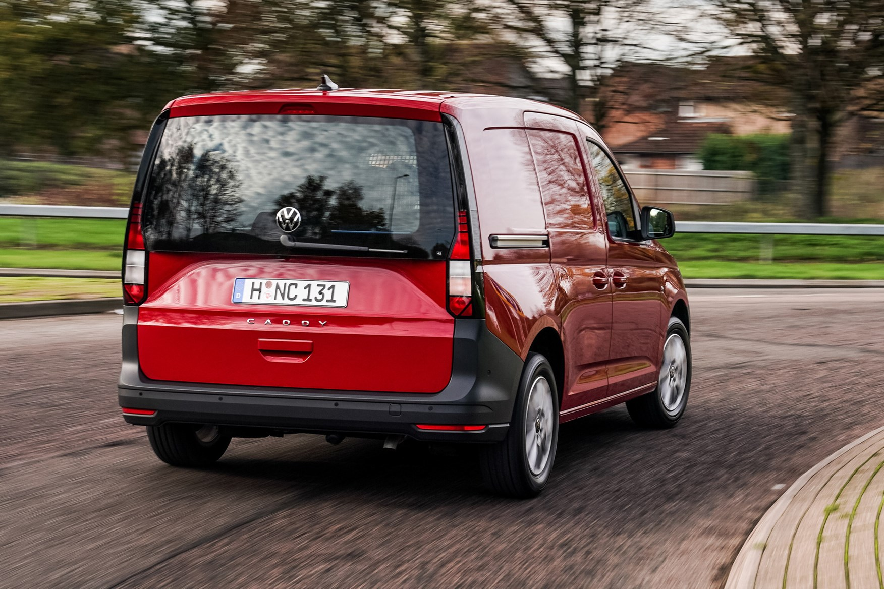 Volkswagen Caddy Cargo review, red, rear view, driving round UK roundabout
